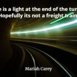 Train tunnel curving to the left with singer Mariah Carey quote: There is a light at the end of the tunnel... Hopefully it's not a freight train!