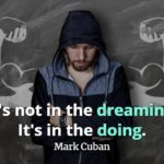 Skinny bearded man with back against a chalkboard drawing of a very muscular man and Mark Cuban quote It's not in the dreaming: It's in the doing.